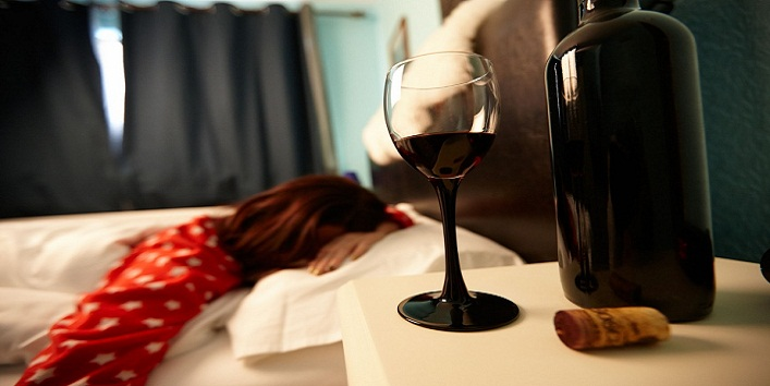 D6A5EW half full glass of wine on bedside table of early twenties woman in bed in a bedroom