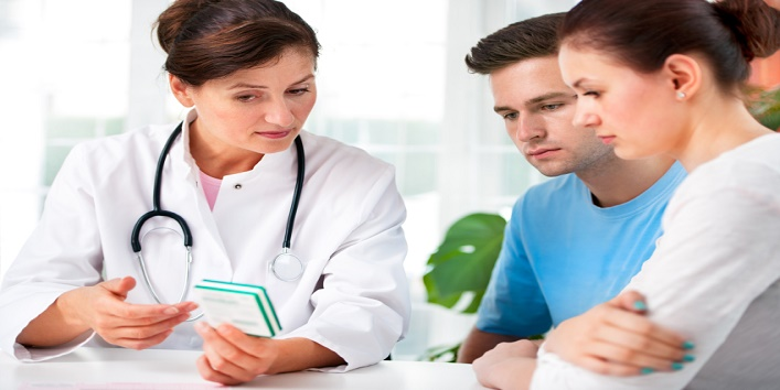 doctor woman offering medical advices to a young couple in office