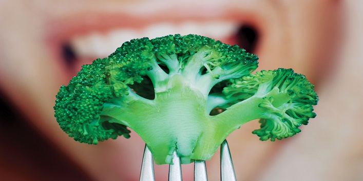 woman eating broccoli floret with fork