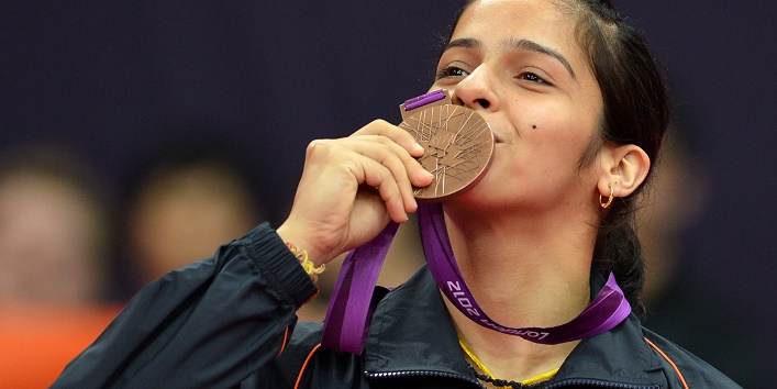 India's Saina Nehwal kisses her bronze medal after beating China's Wang Xin in their bronze medal women's singles badminton match at the London 2012 Olympic Games in London, on August 4, 2012.  AFP PHOTO / ADEK BERRY        (Photo credit should read ADEK BERRY/AFP/GettyImages)