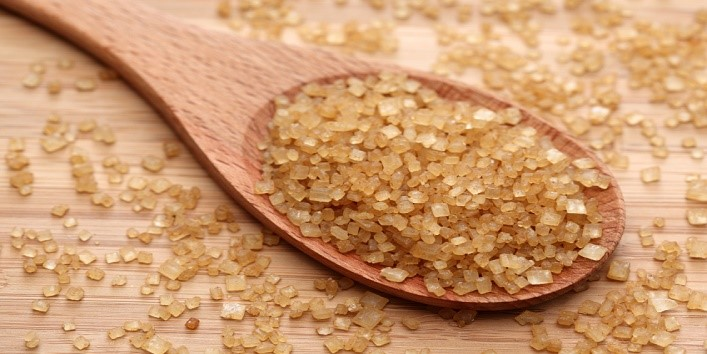Brown cane sugar in a wooden spoon. Close-up.