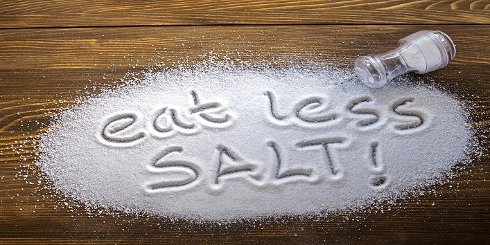 Eat less salt written on a heap of salt - antihypertensive campaign