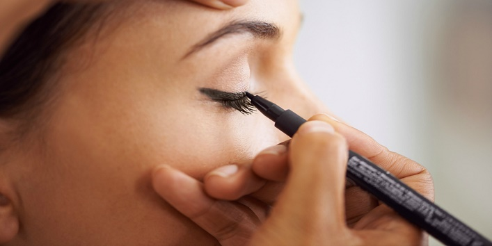 Closeup of a young woman getting liner applied to her eyes