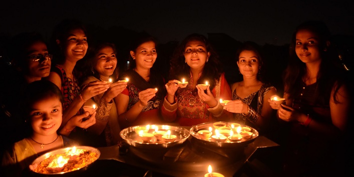 BHOPAL, INDIA - OCTOBER 22: Girls light earthen lamps on the eve of Hindu festival Diwali on October 22, 2014 in Bhopal, India. Prime Minister Narendra Modi has appealed to all Indians that they should buy earthen diyas and lamps from the street sellers instead of imported Chinese lights. Lightning traditional earthen lamps is not only environment friendly but will help in sustaining livelihood of the millions of potters across India who are facing tough time due to increasing use of Fridges and electric lamps. (Photo by Praveen Bajpai/Hindustan Times via Getty Images)
