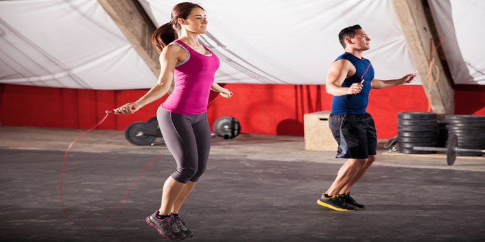 Young man and woman jumping ropes as part of their workout in a crossfit gym