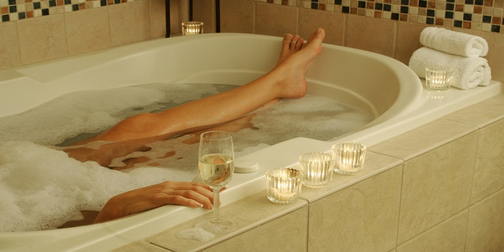 Woman relaxes in a marble tiled bath tub.