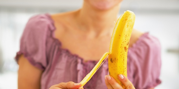 Closeup on young woman peeling banana