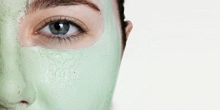 Young woman wearing green facial mask, close-up of eye