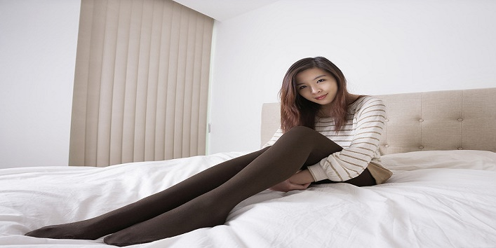 Full length portrait of beautiful young woman in stockings sitting on bed